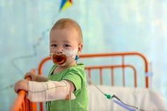 Weinig jongen in het ziekenhuisbed stock foto's