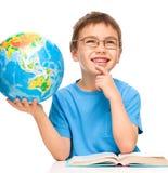 Weinig jongen houdt bol terwijl het dagdromen royalty-vrije stock afbeeldingen