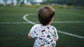 Weinig jongen houdt de bal in zijn handen op het voetbalgebied stock video