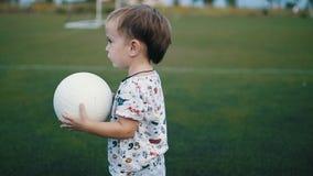 Weinig jongen houdt de bal in zijn handen op het voetbalgebied stock videobeelden