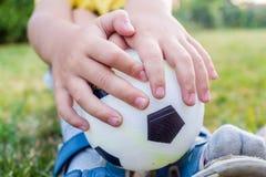 Weinig jongen houdt een bal met zijn beide handen Stock Afbeelding