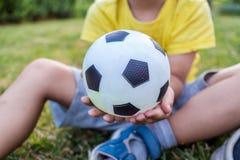 Weinig jongen houdt een bal met zijn beide handen Stock Foto