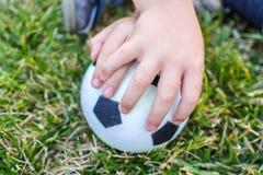 Weinig jongen houdt een bal met zijn beide handen Royalty-vrije Stock Foto's