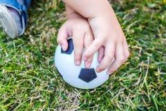 Weinig jongen houdt een bal met zijn beide handen Stock Afbeeldingen
