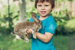 Weinig jongen houdt een konijntje bij het landbouwbedrijf stock fotografie
