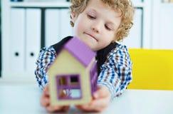 Weinig jongen houdt een plastic huismodel in zijn handen De huizen van onroerende goederen?, Vlakten voor verkoop of voor huur Stock Foto's