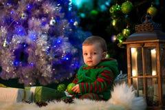 Weinig jongen houdt Kerstmisbal in hand en zit dichtbij Kerstmis royalty-vrije stock fotografie