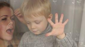 Weinig jongen houdt zijn palm op venster, close-up stock video