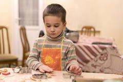 Weinig jongen 4 jaar oud in koekjes van een de oranje schort vormende deeg stock foto's