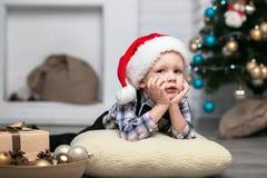 Weinig jongen in Kerstmisdecoratie verwacht een mirakel Stock Foto