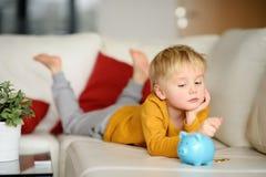 Weinig jongen kijkt op moneybox en plannen van wat hij kan kopen stock afbeeldingen