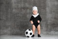 Weinig jongen kijkt opzij verrast, dichtbij een zwart-witte voetbal in zijn benen het dragen van een witte katoenen hoed en zwart royalty-vrije stock foto