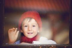 Weinig jongen, kind achter het venster, die hoed en sjaal dragen Stock Afbeelding