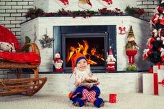 Weinig jongen kleedde zich als de zitting van het Kerstmiself dichtbij de Kerstboom door de open haard, etend koekjes en consumpt Royalty-vrije Stock Foto's