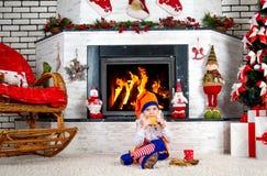 Weinig jongen kleedde zich als de zitting van het Kerstmiself dichtbij de Kerstboom door de open haard, etend koekjes en consumpt Stock Fotografie