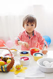 Weinig jongen, kleurende eieren voor Pasen thuis Royalty-vrije Stock Foto's