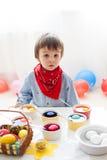 Weinig jongen, kleurende eieren voor Pasen thuis Stock Foto