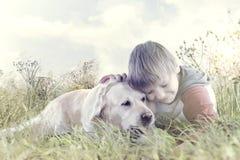 Weinig jongen koestert affectionately zijn hond in het midden van aard royalty-vrije stock afbeeldingen