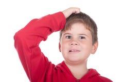 Weinig jongen krast een hoofd royalty-vrije stock foto's