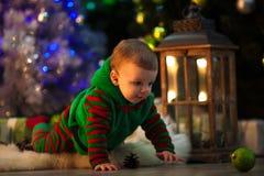 Weinig jongen kruipt aan Kerstmisbal op vloer dichtbij Kerstboom royalty-vrije stock fotografie