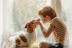 Weinig jongen kust de hond in neus op het venster Vriendschap, auto stock fotografie