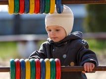 Weinig jongen leert kleuren door gekleurde ringen op de speelplaats te gebruiken Stock Foto's