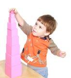 Weinig jongen leert om roze piramide in Montessori te zetten royalty-vrije stock afbeelding