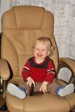 Weinig jongen in leunstoel Stock Foto