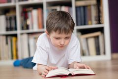 Weinig jongen ligt bij zijn maag en de lezing een boek in de bibliotheek stock foto's