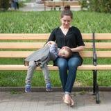 Weinig jongen ligt op zijn zitting van de moeder` s overlapping op de bank Stock Afbeelding