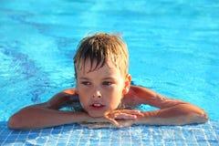 Weinig jongen ligt in zwembad royalty-vrije stock foto
