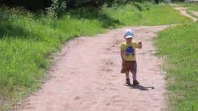 Weinig jongen loopt op bosweg in midden van gras stock footage
