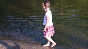 Weinig jongen loopt op water dichtbij meisje het lopen op vijver stock footage