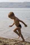 Weinig jongen loopt uit van water Stock Foto's