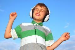 Weinig jongen luistert aan muziek door oortelefoons royalty-vrije stock foto's