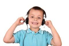 Weinig jongen luistert muziek Stock Afbeelding