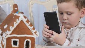 Weinig jongen maakt een foto van peperkoekhuis op smartphone stock footage