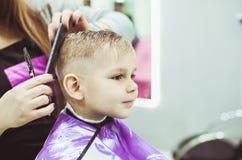 Weinig jongen maakt kapsel bij de kapper stock afbeeldingen