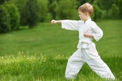 Weinig jongen maakt karateoefeningen Stock Foto's
