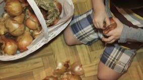 Weinig jongen maakt uien schoon zittend op de vloer in de keuken stock videobeelden