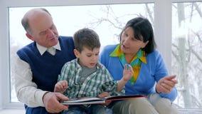 Weinig jongen met boek in handen leert om met grootouders bij vakantie te lezen stock videobeelden