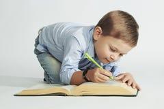 Weinig jongen met boek op de vloer grappige kindschrijver stock afbeelding
