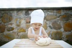 Weinig jongen met chef-kokhoed het koken Stock Afbeeldingen