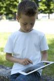 Weinig jongen met de tablet van PC stock foto