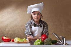 Weinig jongen met de wasgroenten van de chef-kokhoed Stock Afbeeldingen