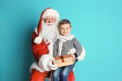 Weinig jongen met de zitting van de giftdoos op de overlapping van Santa Claus ` tegen kleurenachtergrond Royalty-vrije Stock Afbeelding