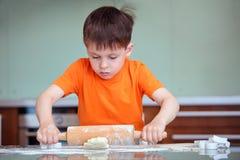 Weinig jongen met deegrollen het bakken Stock Foto's