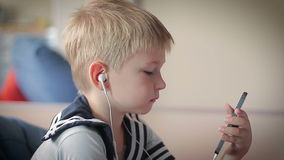 Weinig jongen met een gelukkig gezicht die aan muziek luisteren stock video