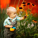 Weinig jongen met een gieter controleert de kwaliteit van bloemen royalty-vrije stock foto
