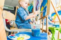 Weinig jongen met een leraar in groep peuterstudent zat de tekening een beeld Schilderend op maelbert, palet en royalty-vrije stock afbeelding